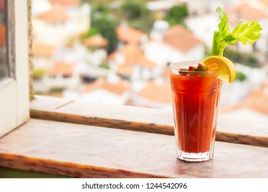 Bloody Mary Cocktail in Glass with Garnish of Olives, Celery, and Lemon in Marble Windowsill with European Town in Background