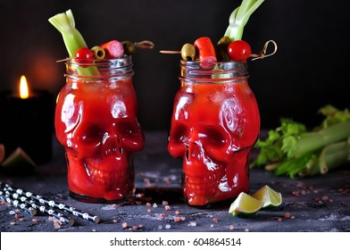 Bloody Mary cocktail in glass skull with celery sticks, pink salt, lime and canapes from canned vegetables.