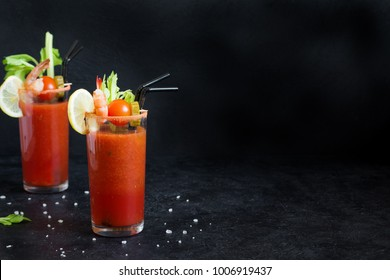 Bloody Mary Cocktail in glasses with garnishes. Tomato Bloody Mary spicy drink on black background with copy space.