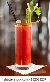 bloody mary cocktail isolated on a busy bar top garnished with onions, olives, asparagus and celery