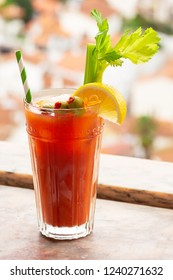 Bloody Mary Cocktail with Lemon, Celery, and Olive Garnish in Glass on Marble Windowsill with Town in Background