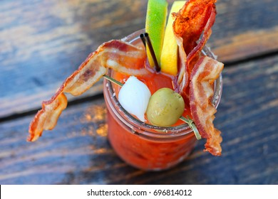 Bloody Mary cocktail with tomato juice and garnish on wooden table