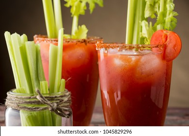 Bloody Mary cocktail with vodka, lemon and tomato juice, tabasco sauce and ice cubes decorated with celery leaves. Focus on the right glass