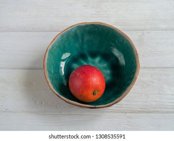 A bloody orange in a ceramic bowl on a white wooden table