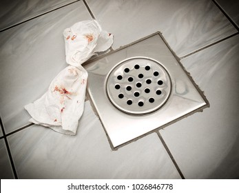 Bloody paper tissue on the floor of a bathroom or toilette.