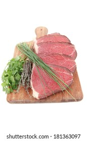bloody raw beef meat on wooden plate with chives and thyme isolated on white background