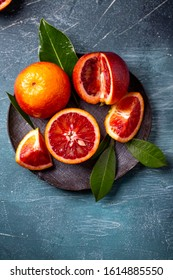 Bloody Sicilian oranges on a green background, whole and pieces with leaves, pattern. top view overhead view  Close up view, copy space