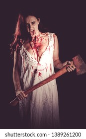 Bloody woman in her night gown holding an axe