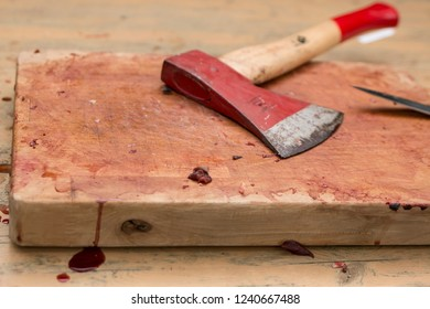 Bloody wooden cutting board on a table with axe and knife