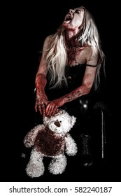 Bloody young woman holding a teddy bear over black background