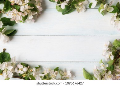 Blooming apple tree branches on wooden background with copy space.