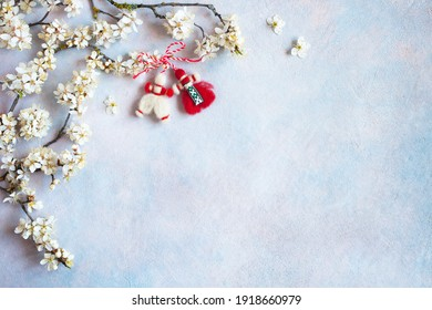 Blooming branches of cherry plums and decor red and white symbol of the holiday of spring March 1 on a decorative background for text, congratulations