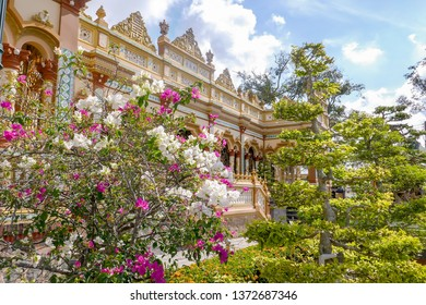 Blooming flowers in front of ornate  Vinh Trang Pagoda in My Tho, Vietnam.