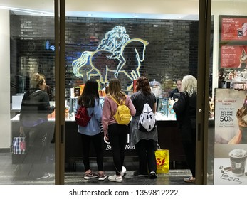Bloomington, MN/USA. March 27, 2019. 5 women look at desserts in a Godiva Belgium 1927 shop in the Mall of America.