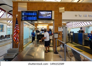 Bloomington,IL/USA-8/25/19: A man putting his luggage on the belt to have them xrayed for guns and bombs at the TSA security check point at a regional airport.