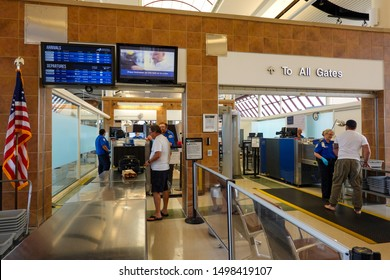 Bloomington,IL/USA-8/25/19: Men  putting their  luggage on the belt to have them xrayed for guns and bombs at the TSA security check point at a regional airport.