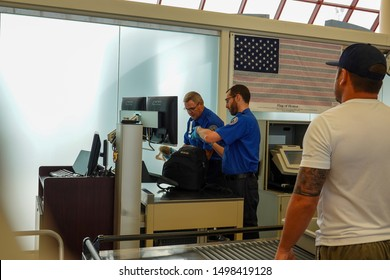 Bloomington,IL/USA-8/25/19: Two TSA Security employees checking a backpack for  potentially dangerous items. at the TSA security check point at a regional airport.