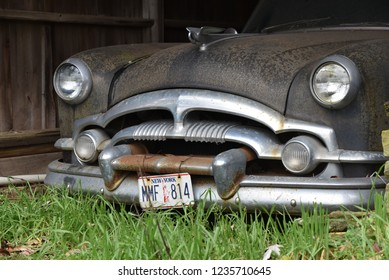 Bloomsburg, PA/USA-Nov. 3, 2018:  Vintage American iconic 1950s automobile, barn find.  Shows close up of grill, headlights and New York license plate, with a hint of a barn wall.