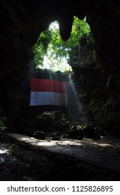 Blora-April 23, 2018:ray of light with indonesian flag in Terawang cave, Todanan, Central Java