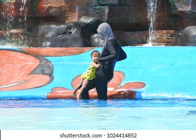 Blora-August 29, 2017: mother and her daughter playing water in the pool on August 20, 2018 in Blora, Central Java, Indonesia