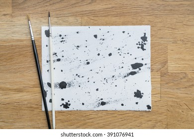 Blots of ink on a white paper on a wooden surface