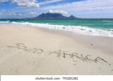 Bloubergstrand with Table Mountain on the far side of Table Bay and text South Africa on the beach