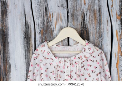 Blouse with ruffle collar and floral pattern. Girls  garment on wooden  hanger over rustic b3485afa0