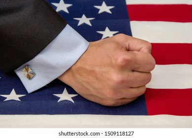 Blow fist on table on which lies American flag, strengthening sanctions, political ambitions, male a suit and shirt with cufflinks
