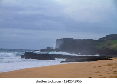 Blowhole spray on cliff faces at beach