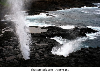 Blowhole throwing a column of water in coastal rock formation - the 'Little Blowhole', Kiama, NSW, Australia.  Copy space.