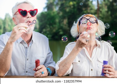 Blowing bubbles. Active funny aged couple standing together and blowing soap bubbles