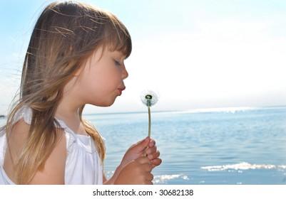 Blowing dandelion on the beach