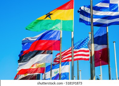 blowing flags of the world behind each other