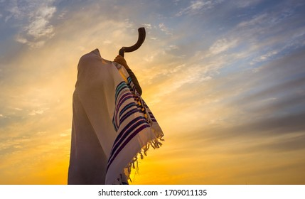 Blowing the shofar for the Feast of Trumpets - Jewish man in a traditional tallit prayer shawl blowing the ram's horn against dramatic sunset sky