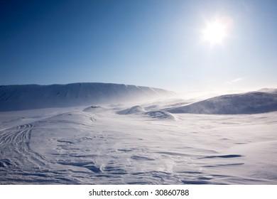 Blowing snow in a barren winter mountain landscape