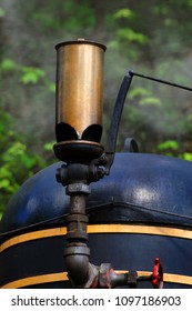 Blowing train whistle throws smoke into the air as train readies for a ride on the train tracks.  Whistle is bronze and train is black.