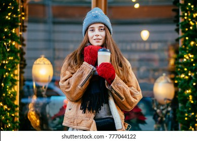 Blown away dreaming woman drinking coffee outdoor in winter city street over beautyful shop window. Christmas, new year, winter holidays concept.