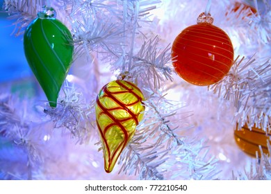 Blown glass Chistmas decorations hanging on a white Christmas tree with twinkle lights strung throughout.