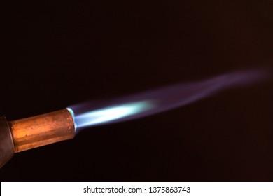 blowtorch blue flame close up dark background