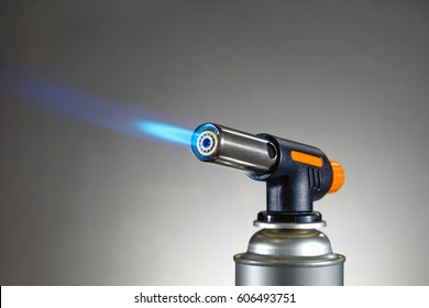 Blowtorch with flame on grey background