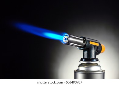 Blowtorch with flame on studio black background