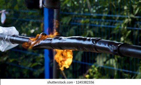 Blowtorch. Frame. Close-up of work with blowtorch on street on background of trees. Roasting of pipes with gas burner