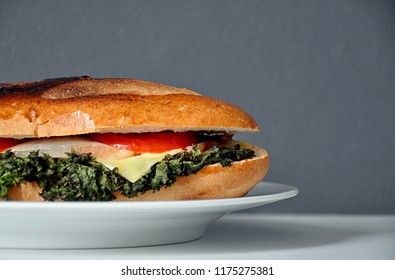 BLT baguette sandwich on white plate and plain backgroud with copy space for text.  Front view close up shot in half.