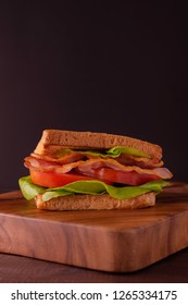BLT Sandwich with Bacon Lettuce and Tomato on wooden board over black background, Homemade meal and fast food.