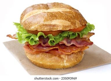 BLT sandwich on pretzel bun. Isolated on white.