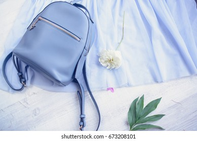 Blu leather backpack with flower on wooden table, top view