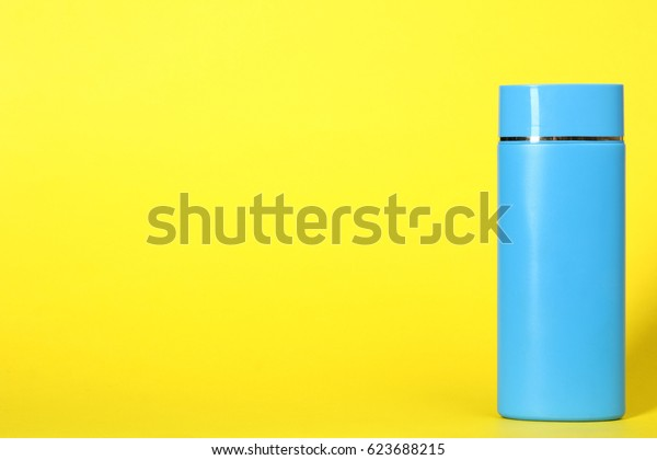 Blua bottle, body lotion on a yellow background