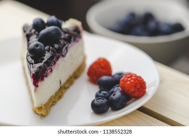 Bluberry cake  is placed on a wood floor with cup of bluberry