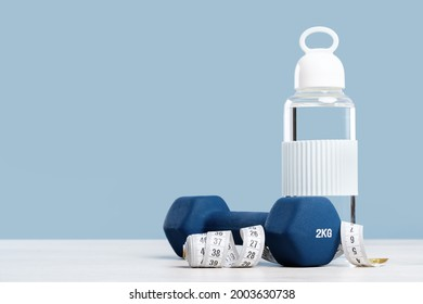 Blue 2 kg dumbbell and measuring tape. Glass water bottle. Workout and exercise fitness weight management and hydration. Blue background. Copy space banner