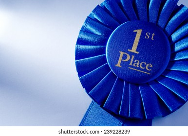 Blue 2nd place winners rosette or badge with a pleated ribbon and gold lettering, close up view over white with copyspace